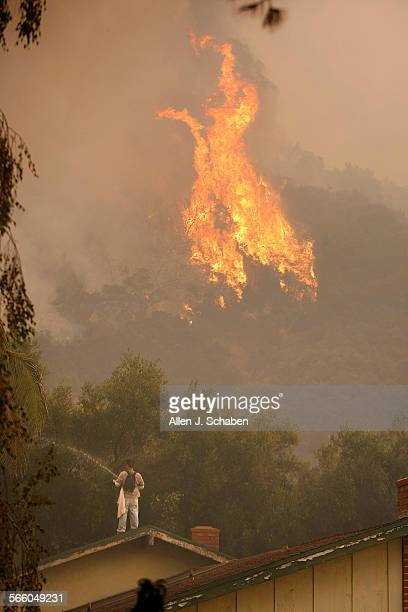 Josh Yeh who's family chose to ignore a mandatory evacuation uses a garden hose to keep his family's roof wet as the Station Fire rages in the...