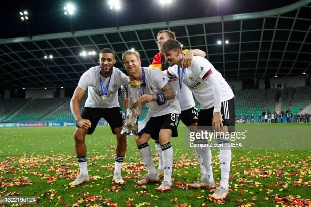 Josha Vagnoman, Arne Maier, Nico Schlotterbecand and Mergim Berisha of Germany celebrate with the UEFA European Under-21 Championship trophy...