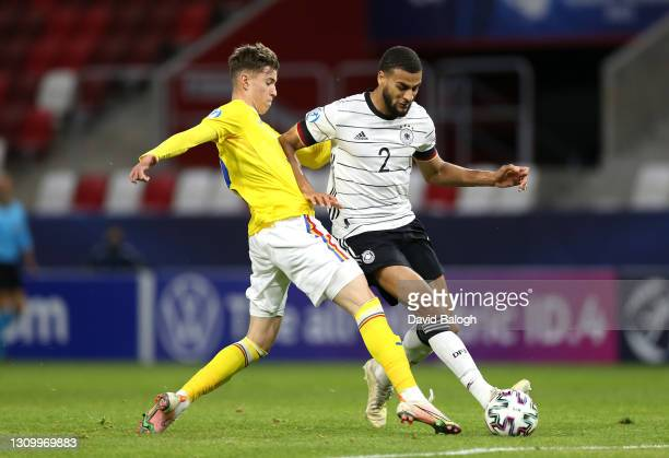 Josha Vagnoman of Germany battles for possession with Octavian Popescu of Romania during the 2021 UEFA European Under-21 Championship Group A match...