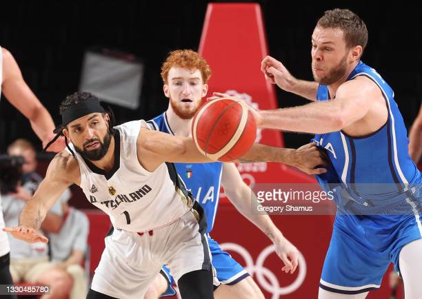 Joshiko Saibou of Team Germany and Nicolò Melli of Team Italy reach for a loose ball during the second half on day two of the Tokyo 2020 Olympic...