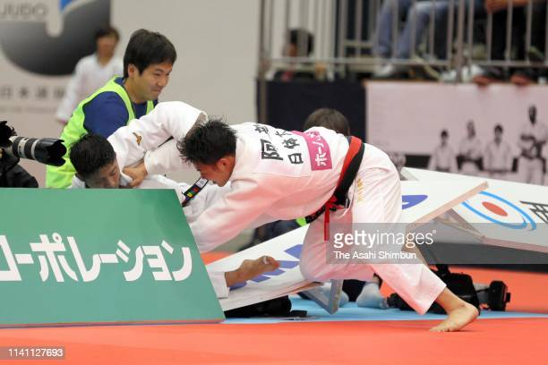Joshiro Maruyama and Hifumi Abe collide in advert boards while competing in the Men's 66kg final during day two of the All Japan Judo Championships...