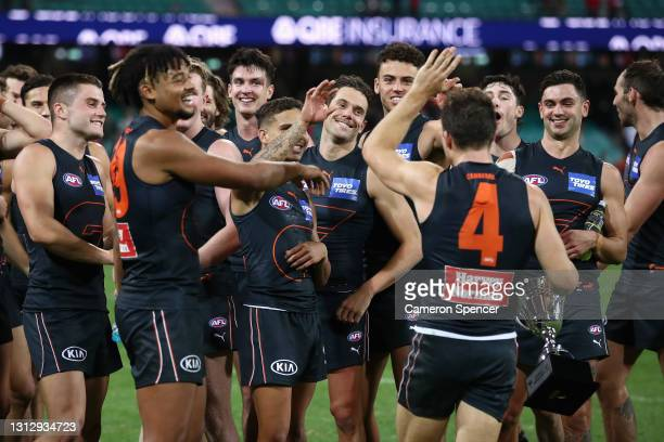 JoshKelly of the Giants and team mates celebrate with TobyGreene of the Giants after winning the round five AFL match between the Sydney Swans and...