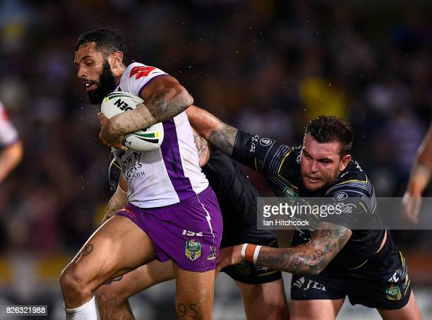 Joshua AddoCarr of the Storm makes a break past Kyle Feldt of the Cowboys which lead to him scoring a try during the round 22 NRL match between the...