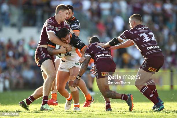 Joshua Aloiai of the Tigers is tackled by the Sea Eagles defence during the round six NRL match between the Manly Sea Eagles and the Wests Tigers at...