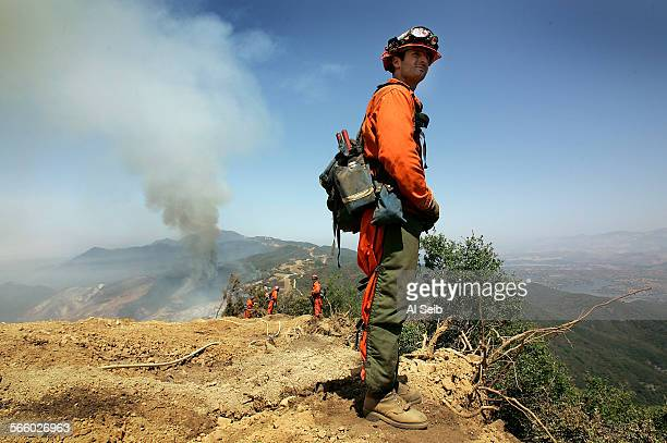 Joshua Ambriz working as a firefighter with Cal Fire and the California Department of Corrections along with fellow firefighters watch the hillside...