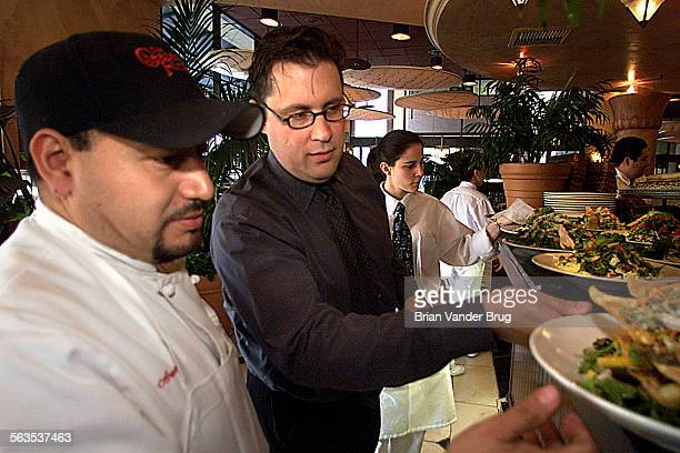 Joshua Armstrong center general manager of The Cheesecake Factory in Woodland Hills checks orders as they come out of the kitchen Thursday afternoon...