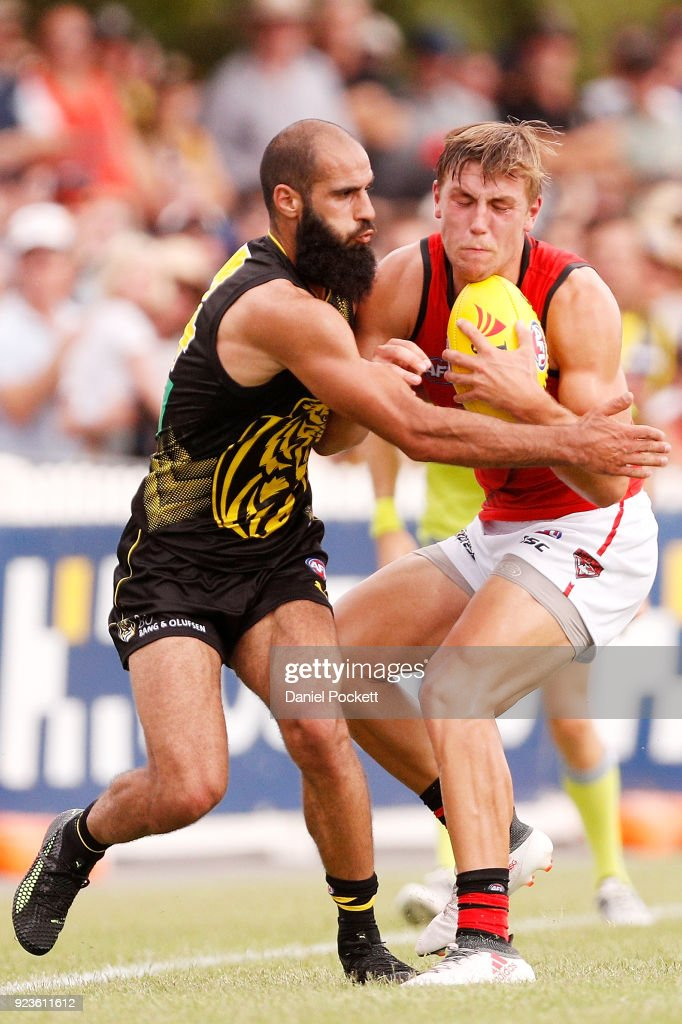 Joshua Begley of the Bombers and Bachar Houli of the Tigers contest the ball during the JLT Community Series AFL match between the Essendon Bombers and the Richmond Tigers at Norm Minns Oval on February 24, 2018 in Wangaratta, Australia.