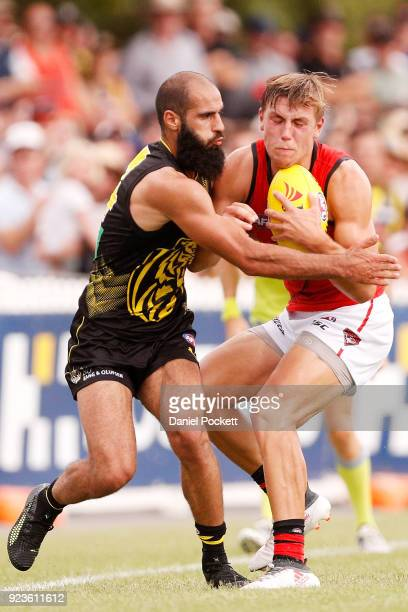 Joshua Begley of the Bombers and Bachar Houli of the Tigers contest the ball during the JLT Community Series AFL match between the Essendon Bombers...