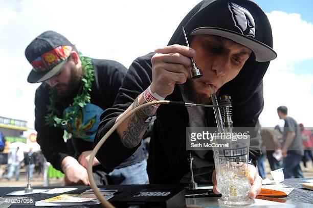 Joshua Brussels of Phoenix Arizona does a dab at the Mini Nail booth during the High Times Cannabis Cup at the Denver Mart in Denver Colorado on...