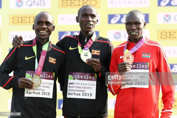 Joshua Cheptegei and Jacob Kiplimo of Uganda and Geoffrey Kamworor of Kenya pose with their medals following the Men's Senior Final during the IAAF...