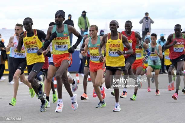 Joshua Cheptegei of Uganda, Guye Idemo Adola of Ethiopia and Jacob Kiplimo of Uganda lead their group during the Men's Final run during the World...