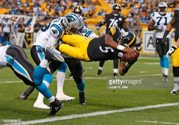 Joshua Dobbs of the Pittsburgh Steelers dives over Rashaan Gaulden and Daeshon Hall of the Carolina Panthers scoring a 3 yard touchdown run in the...