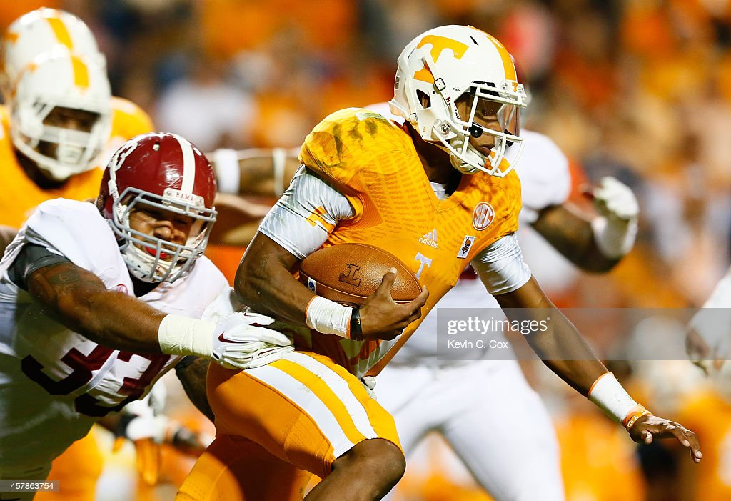 Joshua Dobbs #11 of the Tennessee Volunteers breaks a tackle by Trey DePriest #33 of the Alabama Crimson Tide at Neyland Stadium on October 25, 2014 in Knoxville, Tennessee.