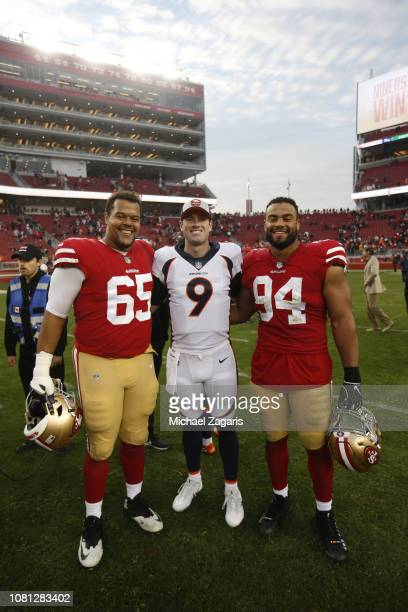Joshua Garnett and Solomon Thomas of the San Francisco 49ers stand on the field with fellow Stanford Alumni Kevin Hogan of the Denver Broncos...