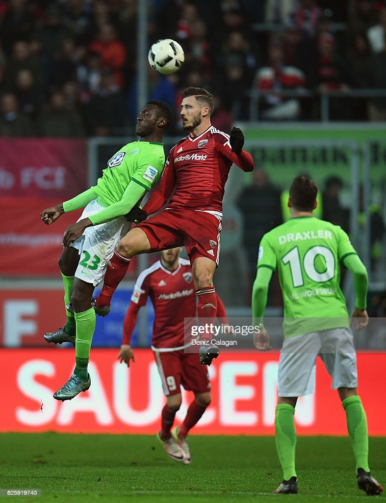 Joshua Guilavogui (l) of Wolfsburg challenges Mathew Leckie (c) of Ingolstadt for a header during the Bundesliga match between FC Ingolstadt 04 and VfL Wolfsburg at Audi Sportpark on November 26, 2016 in Ingolstadt, Germany.