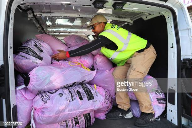 Joshua Holbert manager of operations in Massachusetts for Simple Recycling arranges piles of donated clothes in bags collected in the back of a...