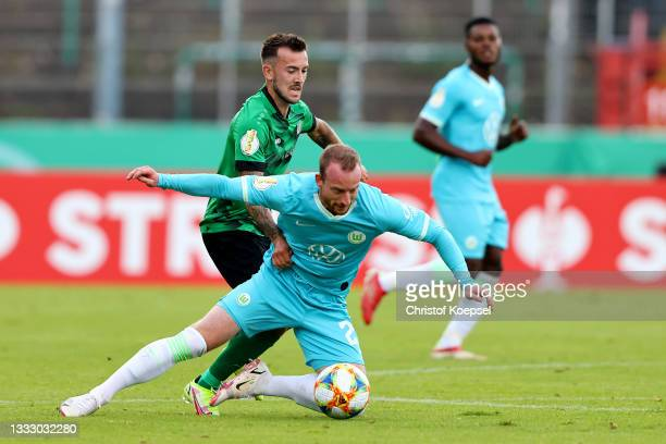 Joshua Holtby of Muenster challenges Maximilian Arnold of Wolfsburg during the DFB Cup first round match between Preußen Münster and VfL Wolfsburg at...