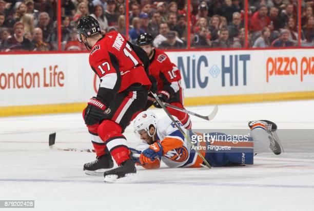 Joshua HoSang of the New York Islanders falls to the ice as Nate Thompson and Tom Pyatt of the Ottawa Senators forecheck against the power play at...