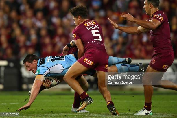 Joshua Jackson of the Blues is tackled during game three of the State Of Origin series between the Queensland Maroons and the New South Wales Blues...