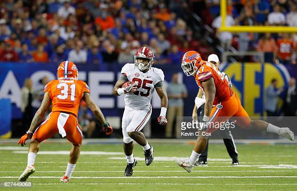 Joshua Jacobs of the Alabama Crimson Tide carries the ball against Teez Tabor of the Florida Gators during the SEC Championship game at the Georgia...