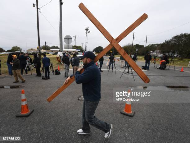 Joshua John Fitch carries a cross past the First Baptist Church which was the scene of the mass shooting that killed 26 people in Sutherland Springs...
