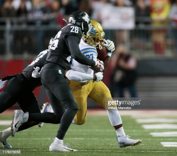Joshua Kelley of the UCLA Bruins carries the ball against Bryce Beekman of the Washington State Cougars in the second half at Martin Stadium on...