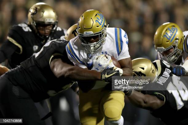 Joshua Kelley of the UCLA Bruins carries the ball in the first quarter against Javier Edwards and Chris Mulumba of the Colorado Buffaloes at Folsom...