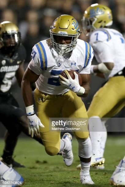 Joshua Kelley of the UCLA Bruins carries the ball in the first quarter against the Colorado Buffaloes at Folsom Field on September 28 2018 in Boulder...