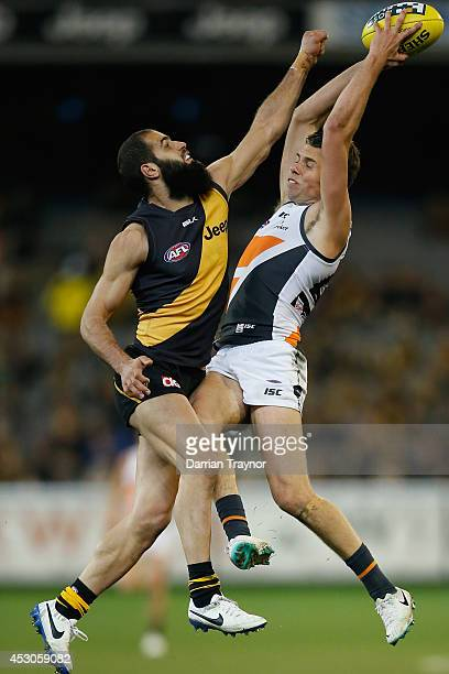 Joshua Kelly of the Giants marks the ball in front of Bachar Houli of the Tigers during the round 19 AFL match between the Richmond Tigers and the...
