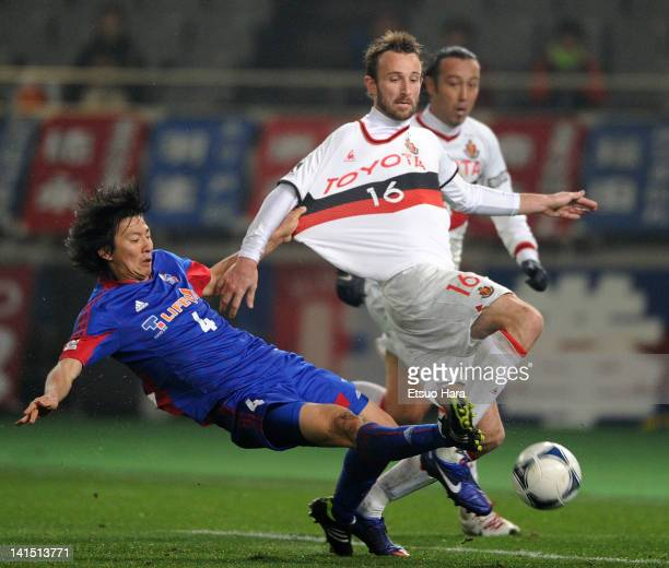 Joshua Kennedy of Nagoya Grampus is tackled by Hideto Takahashi of FC Tokyo during the JLeague match between FC Tokyo and Nagoya Grampus at Ajinomoto...