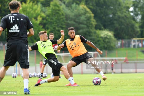 Joshua Kimmich and Corentin Tolisso of Bayern Muenchen compete for the ball during a training session at Saebener Strasse training ground on July 24...