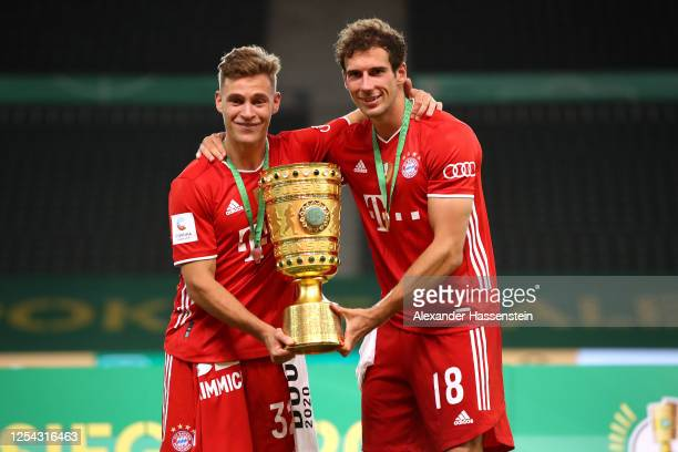 Joshua Kimmich and Leon Goretzka of FC Bayern Muenchen pose with the trophy in celebration after the DFB Cup final match between Bayer 04 Leverkusen...