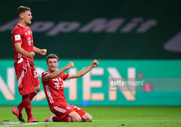 Joshua Kimmich and Thomas Müller of Bayern Muenchen celebrate after winning the DFB Cup final match between Bayer 04 Leverkusen and FC Bayern...