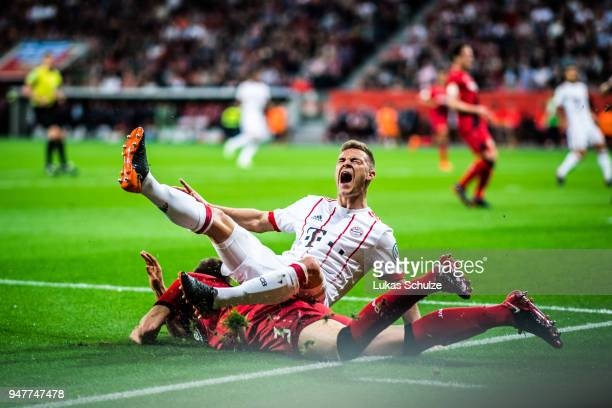 Joshua Kimmich is attacked by Panagiotis Retsos of Leverkusen during the DFB Cup semi final match between Bayer 04 Leverkusen and Bayern Muenchen at...