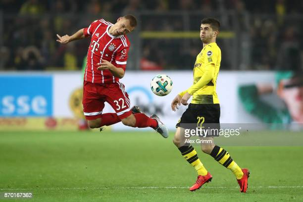 Joshua Kimmich of Bayern Muenchen and Christian Pulisic of Dortmund fight for the ball during the Bundesliga match between Borussia Dortmund and FC...