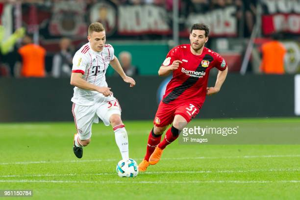 Joshua Kimmich of Bayern Muenchen and Kevin Volland of Leverkusen battle for the ball during the DFB Cup semi final match between Bayer 04 Leverkusen...