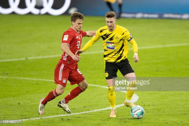 Joshua Kimmich of Bayern Muenchen and Marco Reus of Borussia Dortmund battle for the ball during the Bundesliga match between FC Bayern Muenchen and...