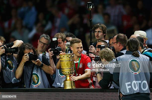 Joshua Kimmich of Bayern Muenchen celebrates victory with the trophy in the dressing room after the DFB Cup final match between FC Bayern Muenchen...
