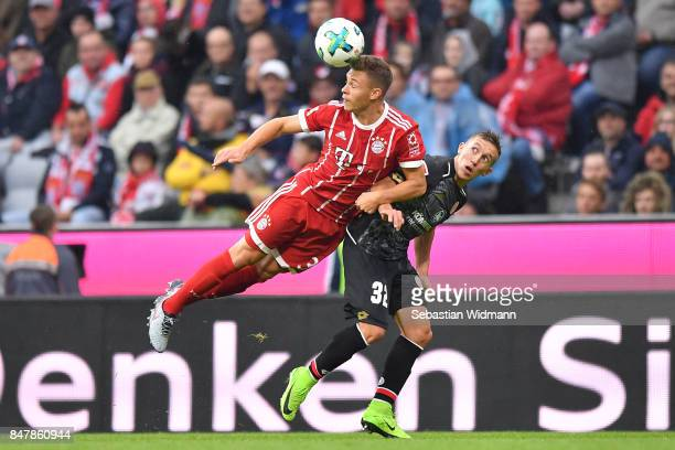 Joshua Kimmich of Bayern Muenchen fights for the ball with Pablo de Blasis of Mainz during the Bundesliga match between FC Bayern Muenchen and 1 FSV...