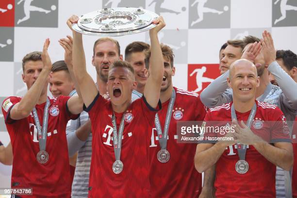Joshua Kimmich of Bayern Muenchen lifts the trophy in Celebration of winning the German Championship title after the Bundesliga match between FC...