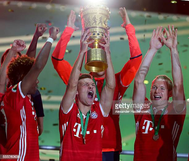 Joshua Kimmich of Bayern Muenchen lifts the trophy with his team mates to celebrate victory after the DFB Cup Final match between Bayern Muenchen and...