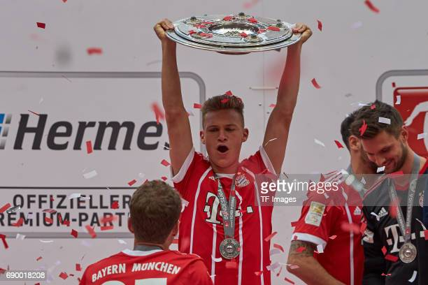 Joshua Kimmich of Bayern Muenchen poses with the Championship trophy in celebration of the 67th German Championship title following the Bundesliga...