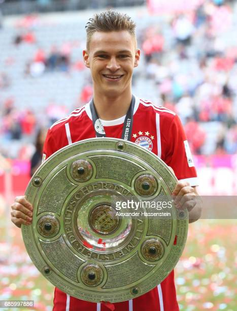 Joshua Kimmich of Bayern Muenchen poses with the trophy following the Bundesliga match between Bayern Muenchen and SC Freiburg at Allianz Arena on...