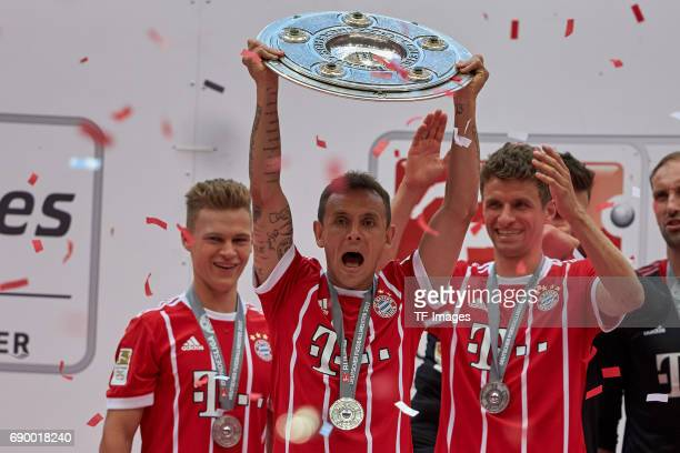 Joshua Kimmich of Bayern Muenchen Rafinha of Bayern Muenchen and Thomas Mueller of Bayern Muenchen poses with the Championship trophy in celebration...