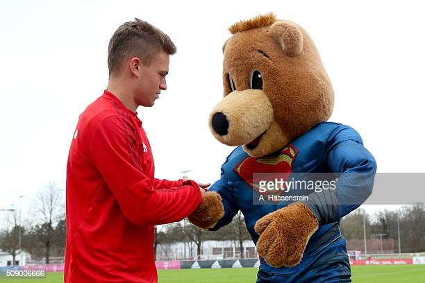 Joshua Kimmich of Bayern Muenchen reacts with mascot Bernie dressed as Superman prior to a training session at Bayern Muenchen's training ground...
