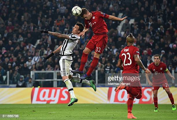 Joshua Kimmich of Bayern Muenchen rises above Mario Mandzukic of Juventus to win a header during the UEFA Champions League round of 16 first leg...