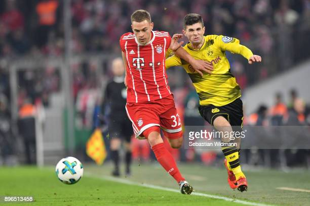 Joshua Kimmich of Bayern Muenchen runs with the ball under pressure from Christian Pulisic of Borussia Dortmund during the DFB Cup match between...