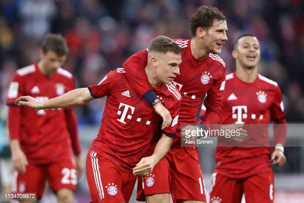 Joshua Kimmich of Bayern Munich celebrates with teammate Leon Goretzka after scoring his team's fifth goal during the Bundesliga match between FC...