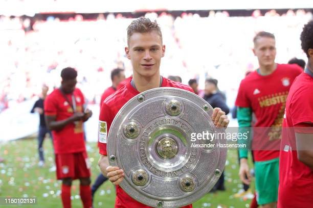 Joshua Kimmich of Bayern Munich celebrates with the trophy following the Bundesliga match between FC Bayern Muenchen and Eintracht Frankfurt at...