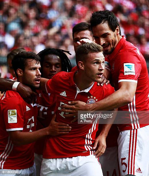 Joshua Kimmich of Bayern Munich is congratulated by Matts Hummels and Juan Bernat after scoring the first goal the Bundesliga match between Bayern...